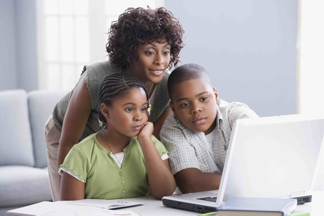 African American mother helping children with homework
