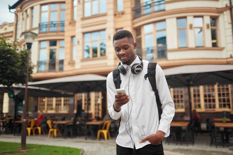 African student walking at street holding one hand in pocket and in other smart phone, writing message. Male with bag and headphones around neck. Looking at electronic map in call phone. Navigation.